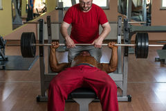 Training in gym where partner gives encouragement.  Stock Photography