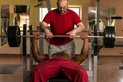 Training in gym where partner gives encouragement. To bodybuilder Stock Photos
