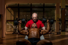 Training in gym where partner gives encouragement. To him Royalty Free Stock Photos