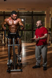 Training in gym where partner gives encouragement. To him Royalty Free Stock Images
