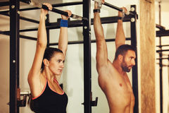 Training in gym. Young and fit couple is training in gym Stock Photos