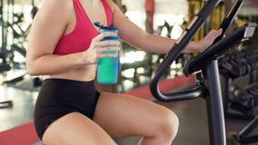 Training in gymnastiek, slank vrouwen drinkwater terwijl het berijden van hometrainer, geschiktheid royalty-vrije stock fotografie