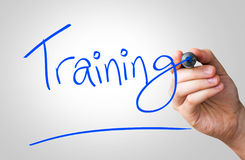 Training hand writing with a blue mark on a transparent board.  Stock Photo