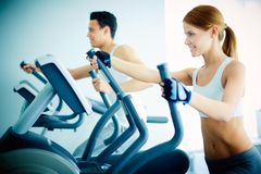 Training in health club. Portrait of pretty girl training on special sport equipment in gym Royalty Free Stock Photos