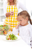 Training for a healthy eating habit. Mother training a healthy eating habit in her child - eating vegetable salad royalty free stock photos