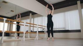 Training im weiblichen Tänzer des Ballsaals Tanzlehrer, der am Barre vor Klasse aufwärmt stock footage