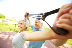 Training with instructor. Senior women exercising with resistance band with instructor royalty free stock photo