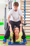 Training instructor. Woman with personal trainer in gym Stock Images