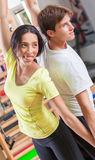 Training instructor. Woman with personal trainer in gym Stock Image