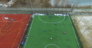 Training junior football team on the sports ground with a green lawn in winter day. Kids team sport outdoors in winter stock footage