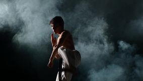 Training Karate or taekwondo man smoke, close up. Karate man with a naked torso and a black belt. doing various exercises hands, smoke. close up, Slow motion stock footage