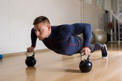 Training with kettlebells. Young man in sportswear practicing push-ups with kettlebells on the floor Stock Images