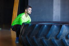 Training a man with a heavy and big tire in the fitness center. Royalty Free Stock Photos