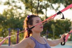 Training met opschortingsriemen in de openluchtgymnastiek, geschikte vrouw opleiding vroeg in ochtend op het park, zonsopgangacht stock fotografie