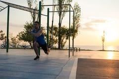 Training mit Traggurten in der Turnhalle im Freien, im starken Mann, der früh am Morgen auf dem Park ausbilden, im Sonnenaufgang  Lizenzfreie Stockfotos