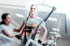 Happy old man learning to walk again. Training muscles. Inspired old grey-haired men smiling and exercising on a training device and learning to walk while a Stock Photos