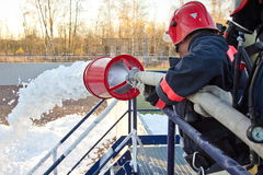 Free Training Of Firemen. The Fireman Extinguishes The Fire With Foam Stock Images - 97479044