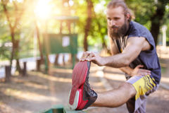 Training outdoors. Young man stretching his legs. Royalty Free Stock Photos