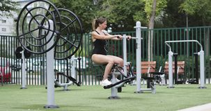 Training in the park. Young woman in black swimsuit and with headphones doing exercises on the simulator stock footage