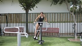 Training in the park. A woman in a black sports swimsuit and headphones on a simulator outdoors. Slow motion stock video