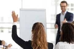 Training participant raise hand ask question at employees team workshop