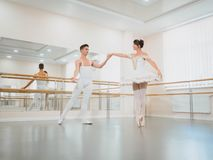 Training before performance. Man dancing classical ballet, he rotating pretty woman in white tutu dress in gym or ballet stock photos