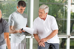 Training plan for senior in gym. Fitness instructor explaining training plan for senior in gym stock photos