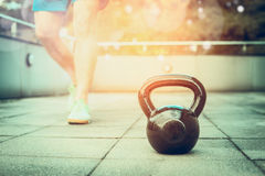 Training process with the kettlebell in the fresh air,  young man trains nature background Royalty Free Stock Photo