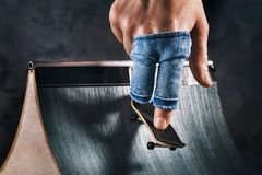 Training process of riding a fingerboard on a ramp. Closeup stock images