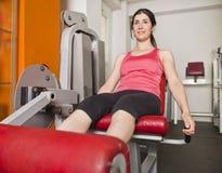 Training quadriceps. Woman doing quadriceps exercises on gym machine Stock Image