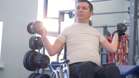 Training session of a disabled man with two dumb-bells in a gym. 4K stock footage