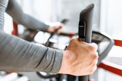 Training on a sports bike in the gym, hand close-up holding the handle of the bike stock photography