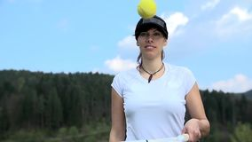 Training stability with bouncing tennis ball. Attractive woman with hat playing with tennis ball and racket in slow motion. Warming up stock footage