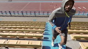 Training on the steps. Black man running up the stairs in the stadium. Steadicam shot. Slow motion. 120fps stock video footage
