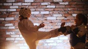Training studio. Martial arts. A girl training her karate kicks on her sister. Mid shot stock footage