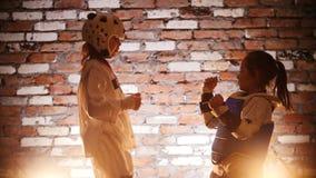 Training studio. Martial arts. A girl training her karate leg kicks on her sister. Mid shot stock video