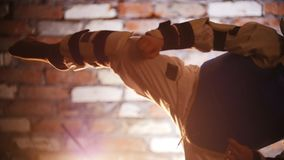 Training studio. Martial arts. Karate training. Kicking the air. Mid shot stock video