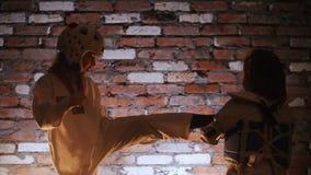 Training studio. Martial arts. Karate. Two little girls fighting. Mid shot stock video