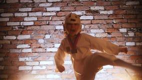 Training studio. Martial arts. Little girl training her karate skills. Showing the kick. Mid shot stock video