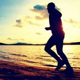 Training at sunset.Running tall man.  A silhouette of jogger at path along lake coastline. Royalty Free Stock Photo