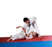 Training techniques nage-waza athletes in kimono. Athletes in kimono training techniques nage-waza Stock Photo