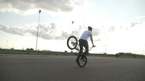 Training of teenage male biker using only his front bike wheel for traction freestyle acrobatic tricks outdoor -. Training of teenage male biker using only his stock footage
