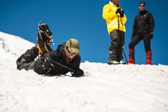 Learning to slip properly on a slope or glacier with an ice ax Stock Photos