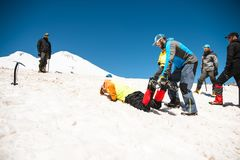 Learning to slip properly on a slope or glacier with an ice ax Stock Photo