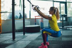 Training with TRX. Young woman in the gym making fitness training Royalty Free Stock Images