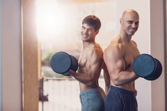 Training two men with dumbbells the arm muscles stock photos