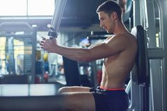 Training Upper Body at Gym. Profile view of concentrated sportsman training upper body with help of pec deck machine, interior of spacious gym on background Stock Images