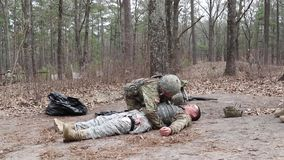 Training US Soldier Controlls Injured Soldier. A female US soldier controlls a injured soldier of he is hit at the boddy through a bullet stock video footage