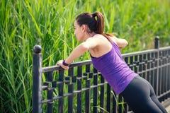 Training van jonge sportieve vrouwen macking oefeningen in park De achtergrond van de aard In purpere t-shirt royalty-vrije stock fotografie