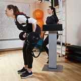 Training with weight sideview. Side view of caucasian women training with weight. Coach standing behind manages electric muscle stimulation purposed to increase Royalty Free Stock Photo